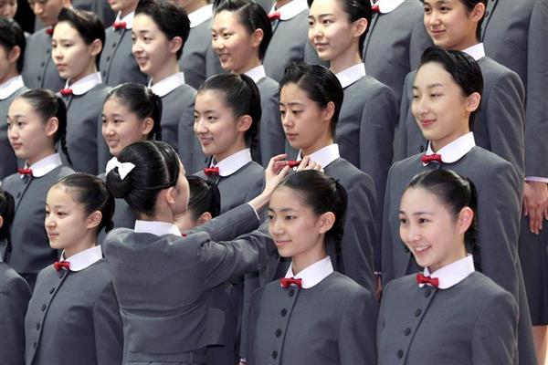 宝塚音楽学校で106期生の入学式が行われる。記念撮影を前に本科生が新入生の服装を正す=17日午前、兵庫県宝塚市(前川純一郎撮影)