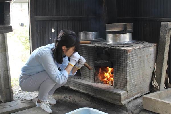 釜戸で米を炊く記者=9日、埼玉県所沢市山口(峯岸祐高さん撮影)
