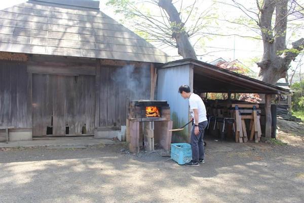 古民家の庭にある釜戸で、ピザを焼く準備をするスタッフの関友洋さん=9日、埼玉県所沢市山口(飯嶋彩希撮影)