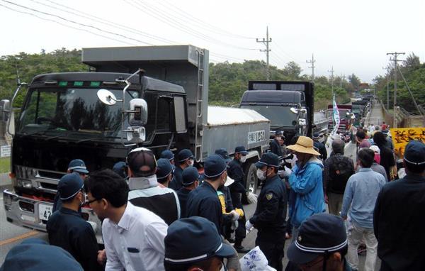 米軍キャンプ・シュワブに搬入されるダンプカーを阻止しようと試みる反対派。後方は渋滞する国道329号線=24日午前、沖縄県名護市(杉本康士撮影)