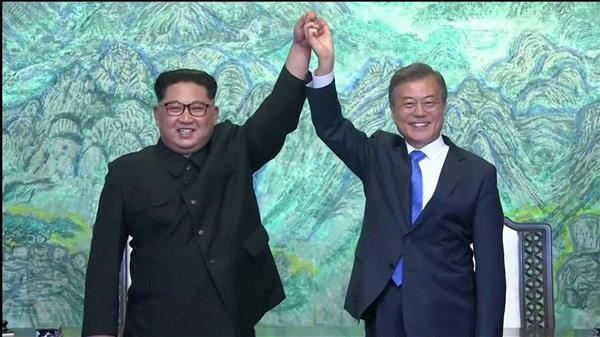 共同宣言に署名し、笑顔を見せる北朝鮮の金正恩朝鮮労働党委員長(左)と韓国の文在寅大統領=27日、板門店の韓国側施設「平和の家」(板門店共同映像取材団)