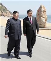 中国国営通信新華社が8日に配信した、中国遼寧省大連で会談に臨む中国の習近平国家主席(右)と北朝鮮の金正恩朝鮮労働党委員長の写真(新華社=共同)