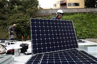 米カリフォルニア州サンフランシスコの住宅の屋根で、太陽光パネルの設置作業を進める様子=9日(ゲッティ=共同)