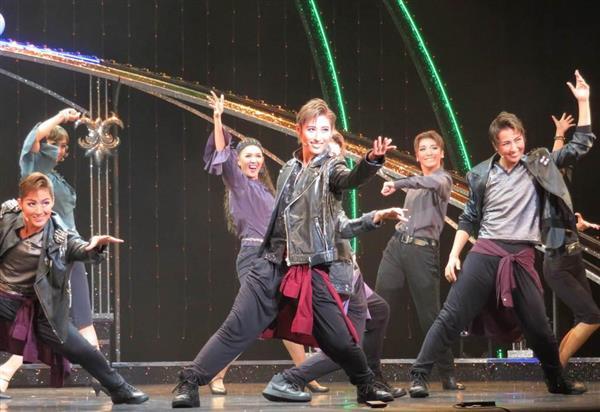1幕の物語仕立てのショーで、人気アーティストグループのリーダー役としてライブ場面を披露する水美舞斗(中央)