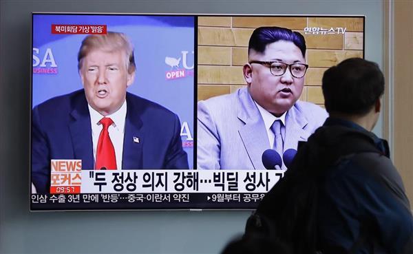 トランプ米大統領(左)と金正恩朝鮮労働党委員長が映ったニュース映像=11日、ソウル(AP)