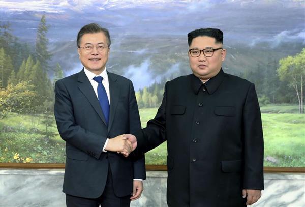 板門店で開かれた南北首脳会談で握手する韓国の文在寅大統領(左)と北朝鮮の金正恩朝鮮労働党委員長=26日(韓国大統領府提供・共同)