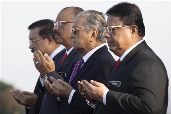 首相府スタッフと祈りをささげるマハティール氏(左から3人目)=21日、クアラルンプール近郊のプトラジャヤ(AP)