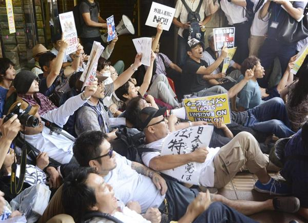 川崎市の市教育文化会館で開催予定だった集会に抗議し、座り込む反対派市民ら=3日午後