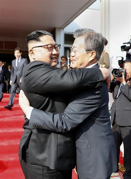 5月26日、板門店で抱き合う北朝鮮の金正恩朝鮮労働党委員長(左)と韓国の文在寅大統領(韓国大統領府提供・共同)