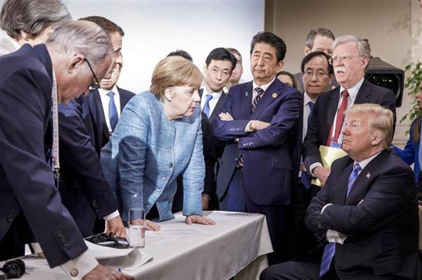 G7サミットで、トランプ米大統領(右端)に向かい、机に手を置いて討議するドイツのメルケル首相(中央左)。メルケル氏の横で腕組みする安倍首相=9日、カナダ・ケベック州(ドイツ政府提供、AP)