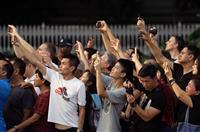 大統領官邸に入る北朝鮮の金正恩朝鮮労働党委員長を乗せたとみられる車列を撮影しようとする人たち=10日午後、シンガポール(松本健吾撮影)