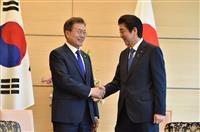 握手する安倍首相(右)と文在寅・韓国大統領=5月9日、東京都千代田区(ロイター)