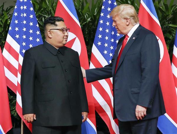 会談の冒頭で向き合う北朝鮮の金正恩朝鮮労働党委員長(左)とトランプ米大統領=12日、シンガポール(AP)