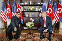 北朝鮮の金正恩朝鮮労働党委員長(左)との会談で指を立てるトランプ米大統領=12日、シンガポール(AP=共同)