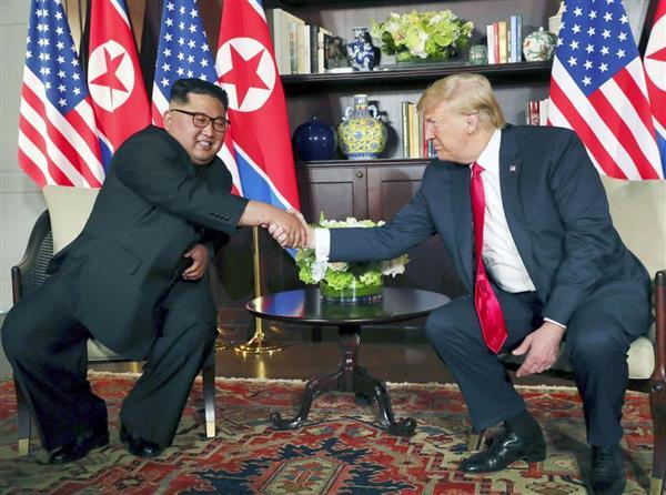 会談で握手する北朝鮮の金正恩朝鮮労働党委員長(左)とトランプ米大統領=12日、シンガポール(ロイター=共同)