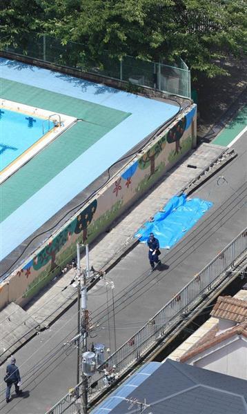 プール横の塀が倒壊した寿栄小学校の現場 =18日午前10時、大阪府高槻市(本社ヘリから、恵守乾撮影)