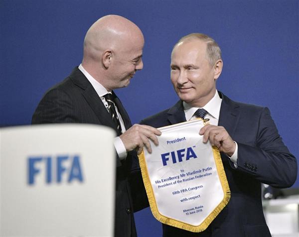 FIFA総会でロシアのプーチン大統領(右)にペナントを手渡すインファンティノ会長=13日、モスクワ(ロイター)