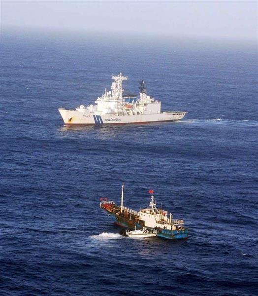 小笠原諸島の周辺海域を航行するサンゴ密漁の中国漁船(手前)=平成26年10月5日(海上保安庁提供)