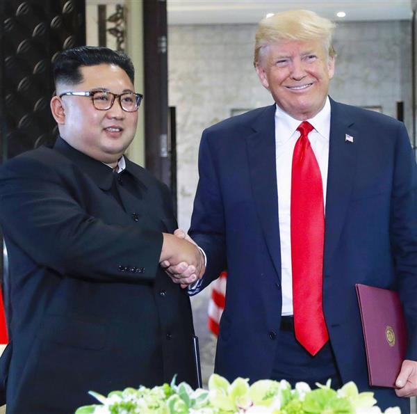 12日、首脳会談で合意文書を交換し、握手する北朝鮮の金正恩朝鮮労働党委員長(左)とトランプ米大統領=シンガポール(AP)