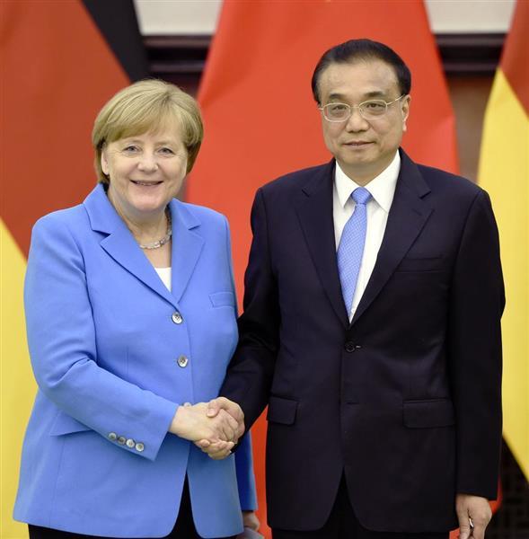 5月24日、共同会見を終え握手するドイツのメルケル首相(左)と中国の李克強首相=北京の人民大会堂(共同)