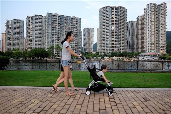 中国の大企業「アジャイル・プロパティ」によって開発されたマンション群を歩く母子=6月27日、広東省中山(ロイター)