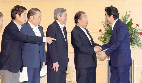 西日本豪雨の被災者への支援対策を申し入れに来た自民党の二階俊博幹事長(右から2人目)らを笑顔で迎えた安倍晋三首相(右)=7月17日、首相官邸(春名中撮影)