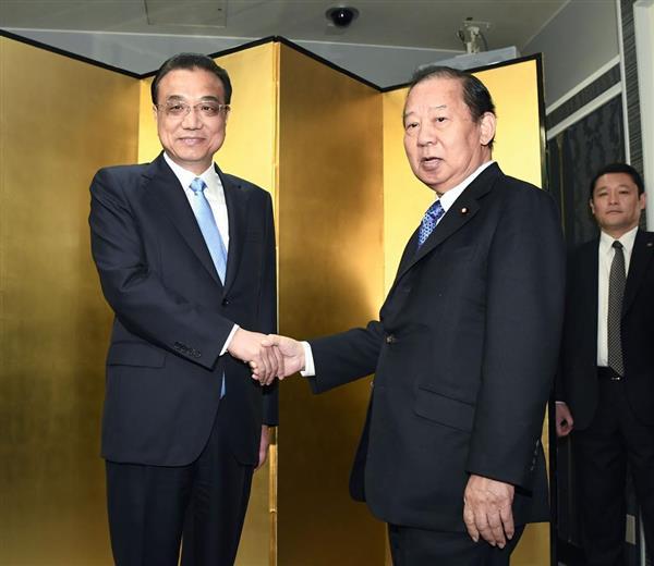 5月10日、来日した中国の李克強首相(左)と握手する自民党の二階俊博幹事長=東京都千代田区(代表撮影)