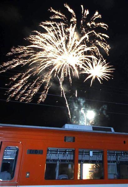打ち上げ花火を停止した車内から見物する一畑電車の「花火列車」