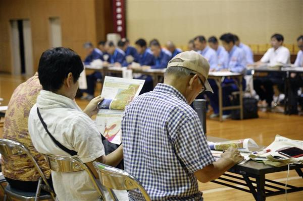 愛媛県西予市で開かれた住民説明会で資料に目を通す住民ら=9日夜