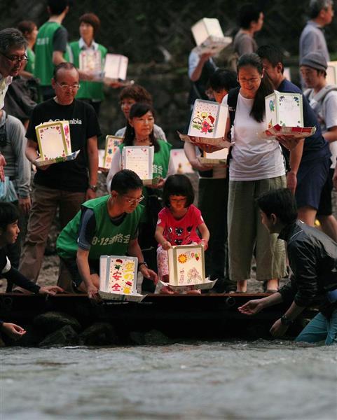 日航ジャンボ機墜落事故から12日で33年となるのを前に、「御巣鷹の尾根」の麓の神流川に灯籠を流す子どもら=11日夕、群馬県上野村