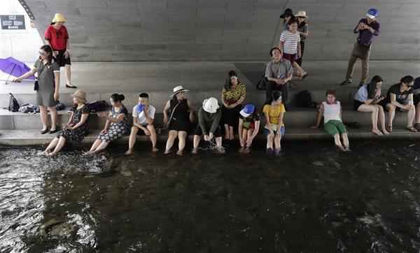 暑さから逃れてソウル市中心部を流れる清渓川の日陰で休む韓国市民(AP)
