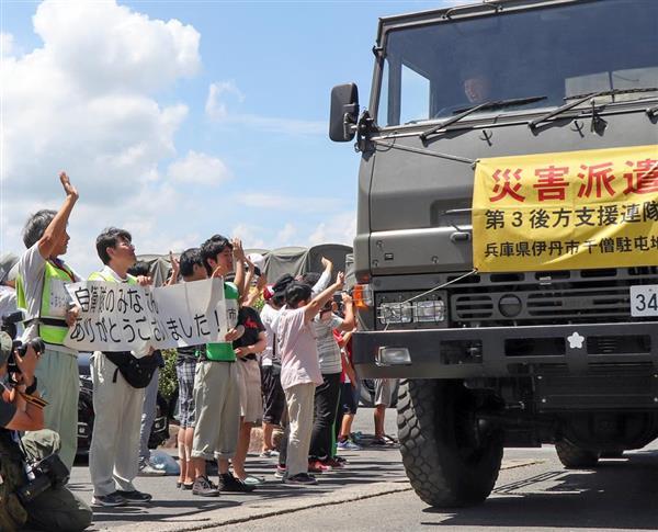 真備町地区の避難住民らの見送りを受けて引き揚げる自衛隊の車両=倉敷市