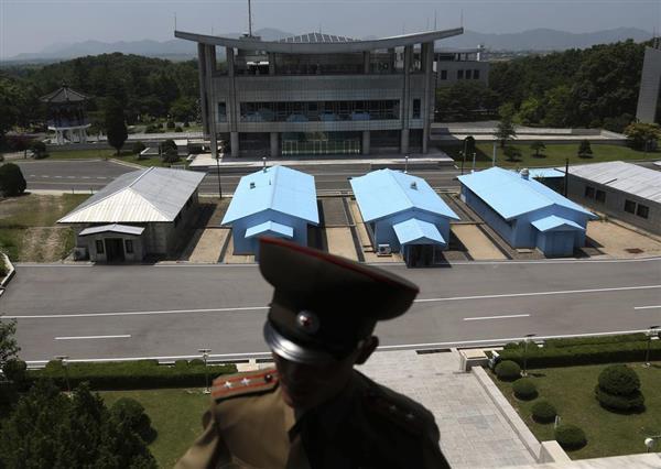 板門店の非武装地帯を警備する北朝鮮兵(手前)。奥に韓国の施設が見える=板門店(AP)