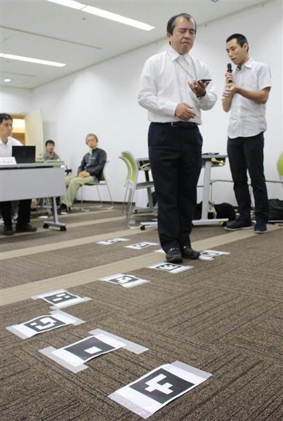 電車の乗車位置などを教える音声アプリを紹介する視覚障害者ら=神戸市中央区