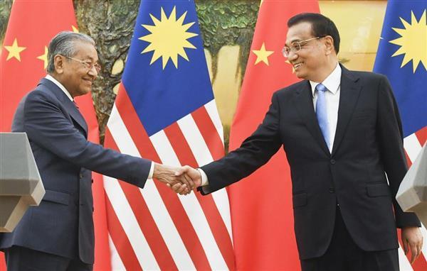 共同記者会見を終え、握手するマレーシアのマハティール首相(左)と中国の李克強首相=20日、北京の人民大会堂(共同)