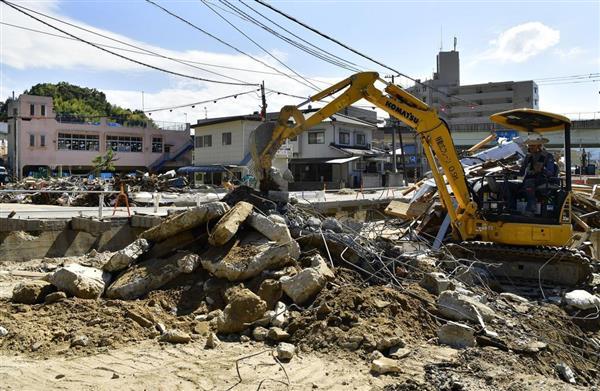 西日本豪雨の影響でたまったがれきを撤去する作業員=広島県呉市