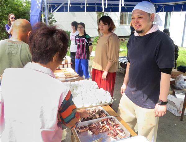炊き出しで被災者に手料理をすすめる三上寛人さん=8日午後、北海道厚真町(中村昌史撮影)