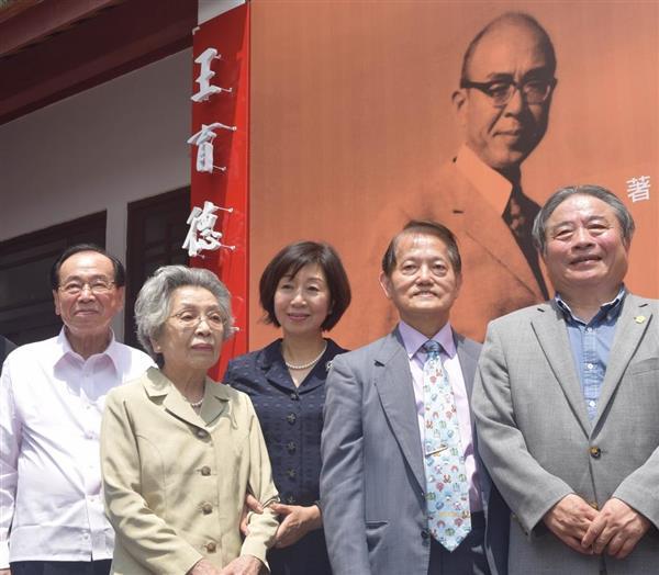9日、台湾南部・台南市で、除幕された王育徳記念館の看板の前に立つ妻の王雪梅さん(左から2人目)と次女の王明理さん(中央)=田中靖人撮影