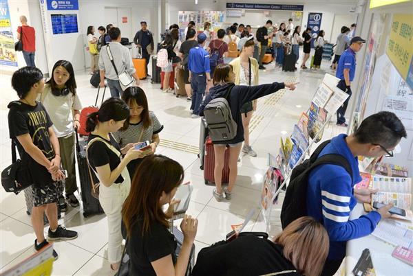 関西国際空港第2ターミナル国際線到着口でインフォメーションのカウンターに並ぶ外国人ら=11日午後(永田直也撮影)