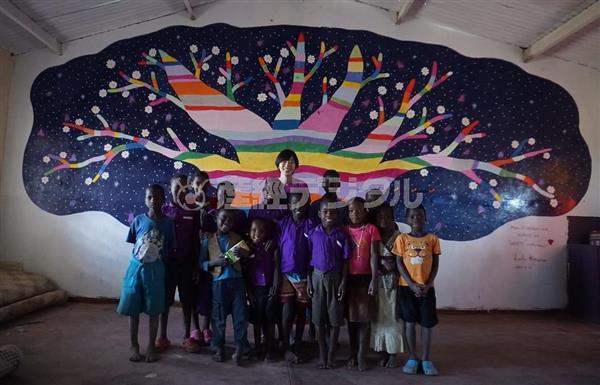 完成した壁画の前で子供たちと記念撮影する河野ルル(中央)=本人提供