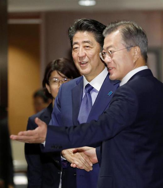 会談前に韓国の文在寅大統領(右)と笑顔で握手する安倍首相=25日、ニューヨーク(共同)