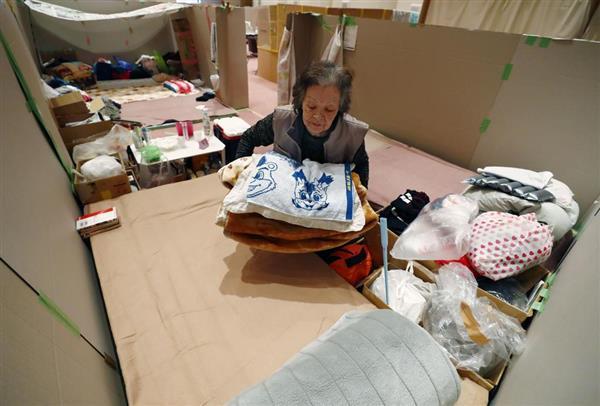 避難所で毛布を手にする女性。支給された毛布では薄く、厚手のものを自宅から持ってきた=27日午前、北海道安平町