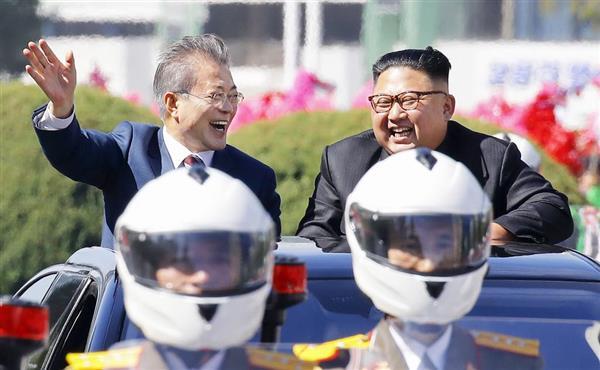 平壌市内をパレード中に笑顔を見せる韓国の文在寅大統領(左)と北朝鮮の金正恩朝鮮労働党委員長=18日(平壌写真共同取材団)