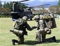 共同訓練でCH46輸送ヘリに搭乗前、陸上自衛隊の隊員(左)と握手を交わす英陸軍の兵士=2日午前、静岡県小山町の陸自富士学校(酒巻俊介撮影)