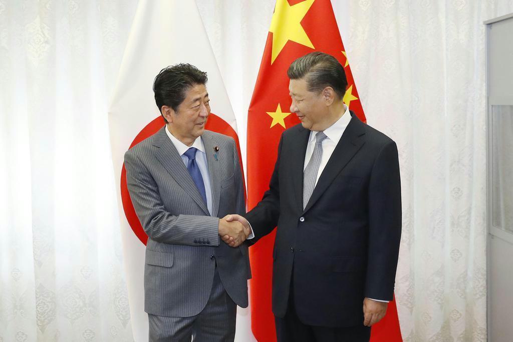 日中首脳会談で握手する、中国の習近平国家主席(右)と安倍晋三首相=9月12日、露ウラジオストク