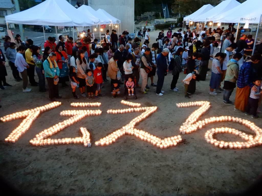 「伝える」の文字をともしたキャンドルの前で西日本豪雨の犠牲者に黙祷を捧げる被災者やボランティアら=20日、広島県坂町小屋浦(有年由貴子撮影)