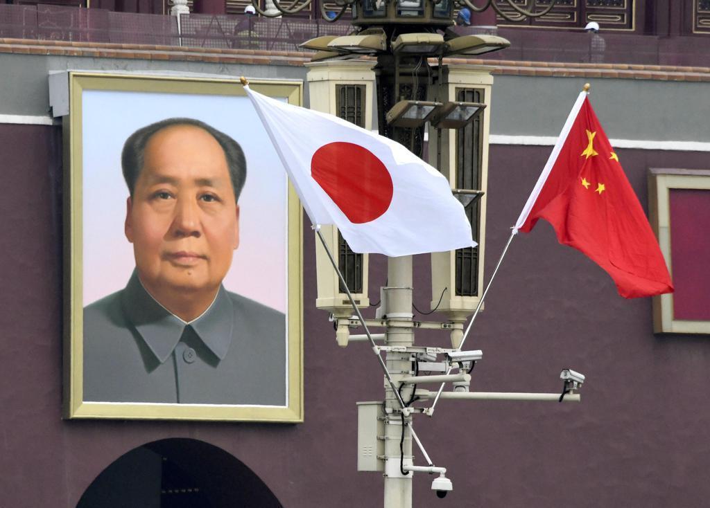 安倍首相の公式訪問を前に北京の天安門広場に掲げられた日の丸。奥は毛沢東の肖像画=25日(共同)