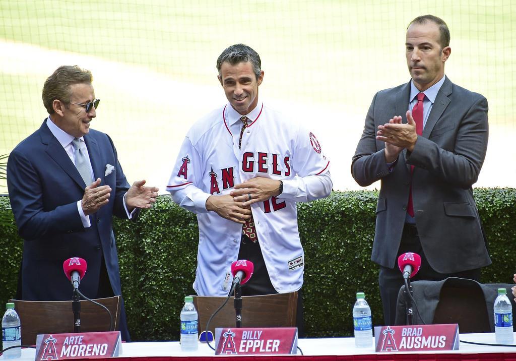 記者会見で紹介されるエンゼルスのブラッド・オースマス新監督。左はモレノ・オーナー、右はエプラーGM=22日、アナハイム(ゲッティ=共同)