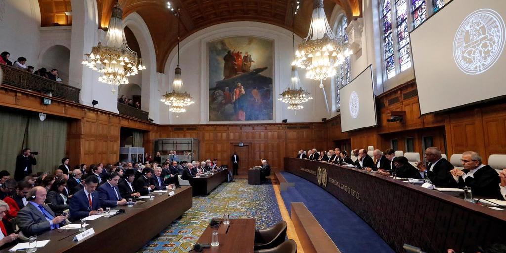 国際司法裁判所の法廷。南米ボリビアとチリの訴訟で、ボリビアのエボ・モラレス大統領(左)とチリの代理人弁護士が出廷している=10月1日、オランダ・ハーグ(ロイター)