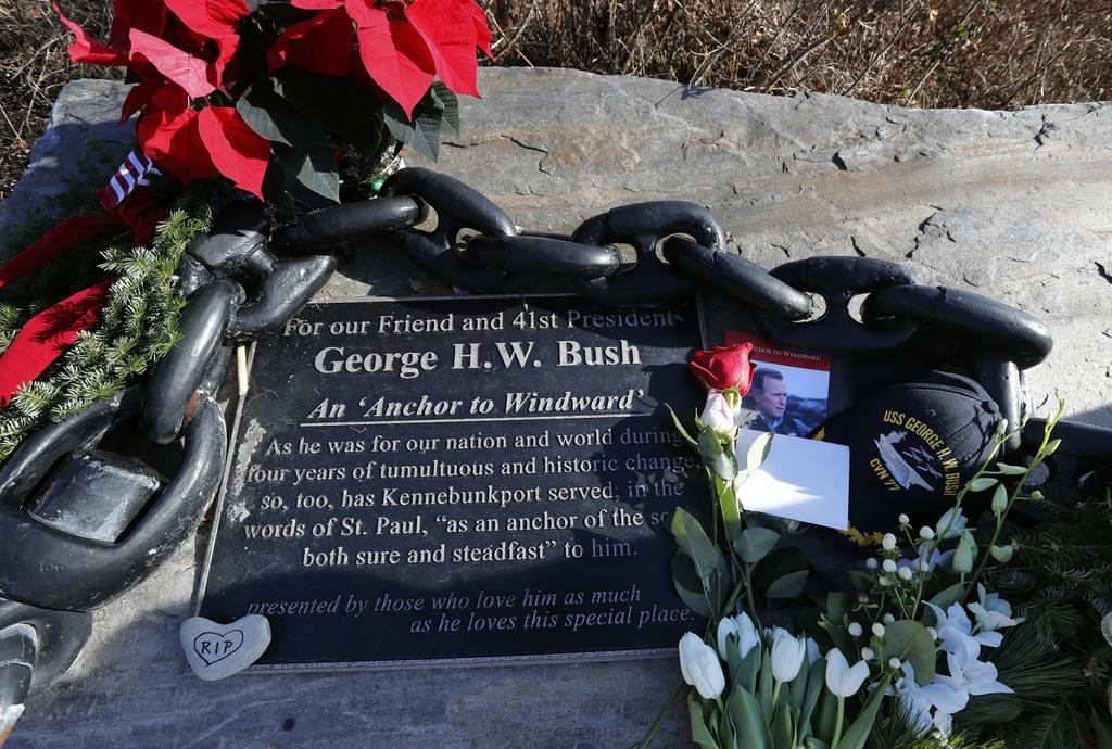 ブッシュ家が夏に滞在する邸宅前に設置されたジョージ・H・W・ブッシュ氏の功績をたたえるプレートに置かれた花や写真=1日、メイン州ケネバンクポート(AP)